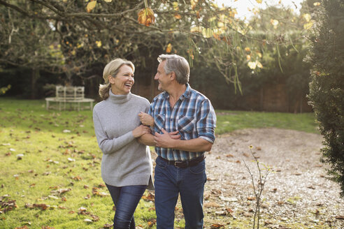 Happy, carefree mature couple walking arm in arm in sunny autumn backyard - HOXF03725