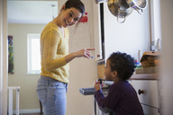 Playful mother and son in kitchen - HOXF03764
