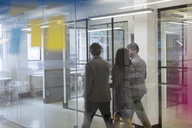 Business people walking and talking in office corridor - CAIF21310