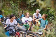 Friends mountain biking, resting in woods - CAIF21316