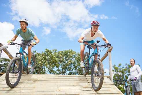 Focused men mountain biking on obstacle course ramp - CAIF21331