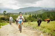 Man mountain biking with friends on rural dirt road along cow pasture - CAIF21334