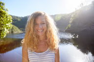 Portrait smiling, confident young woman at sunny summer lake - CAIF21346