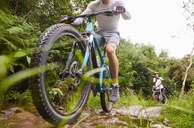 Man mountain biking on muddy trail - CAIF21349