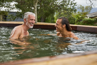 Father and son relaxing in hot tub - CAIF21352