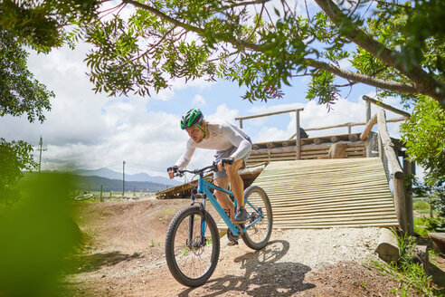 Focused man mountain biking down sunny obstacle course ramp - CAIF21355