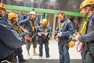 Zip line instructor and students preparing equipment - CAIF21406