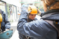Woman helping friend with zip line helmet - CAIF21415