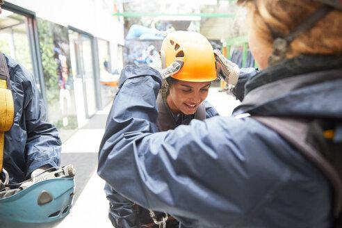 Woman helping friend with zip line helmet - CAIF21415