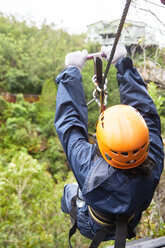 Woman zip lining above trees - CAIF21421
