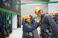Woman helping man with zip line equipment - CAIF21424