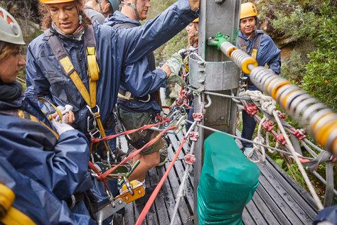 People preparing zip line equipment - CAIF21427