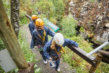 Friends walking on bridge, preparing to zip line - CAIF21436