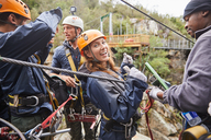 Portrait smiling, confident young woman preparing to zip line - CAIF21439