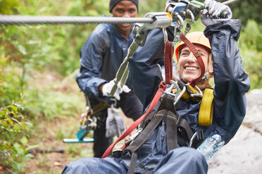 Smiling young woman zip lining - CAIF21442