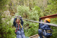 Woman zip lining above trees - CAIF21445