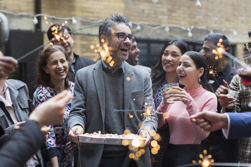 Friends celebrating birthday with cake and sparklers - CAIF21448