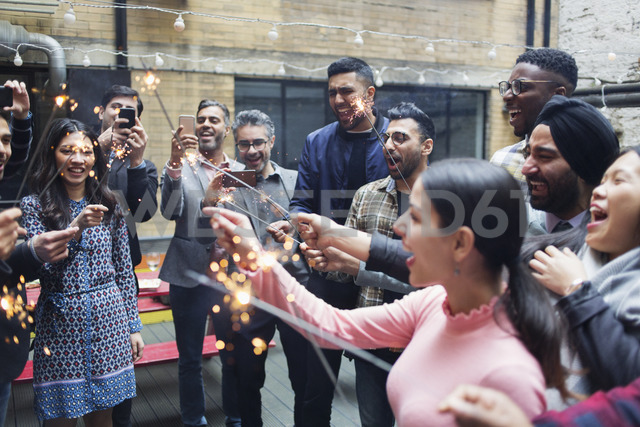 Friends enjoying party, celebrating with sparklers - CAIF21454