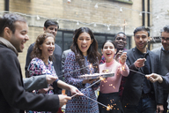 Friends celebrating with woman holding birthday cake - CAIF21466