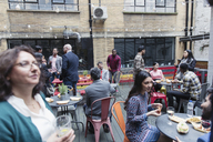 Friends socializing, eating and drinking at party on patio - CAIF21475