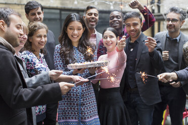 Friends with sparklers celebrating with woman holding birthday cake - CAIF21478