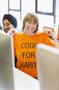 Portrait confident hacker wearing t-shirt, coding for charity at hackathon - CAIF21496