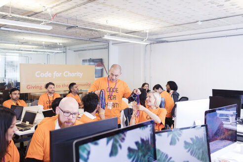 Hackers with lanyards coding for charity at hackathon - CAIF21502