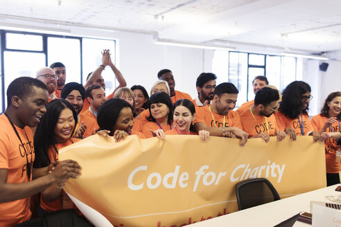 Hackers with banner coding for charity at hackathon - CAIF21508