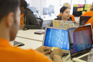Hackers at laptops coding for charity at hackathon - CAIF21517