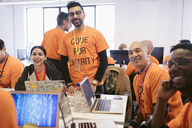 Portrait confident hackers coding for charity at hackathon - CAIF21523