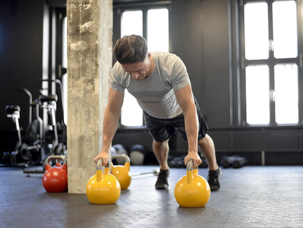 Man doing pushups on kettlebells at gym - BFRF01892