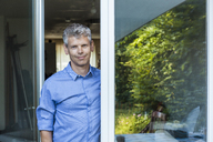 Portrait of mature man with grey hair standing at open terrace door - TCF05642