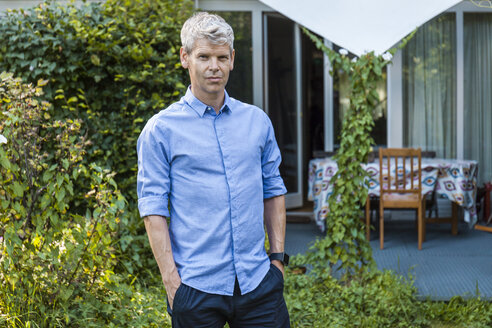 Portrait of mature man with grey hair standing in garden of his house - TCF05645