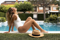 Young woman wearing a swimsuit sitting at the pool - ACPF00267
