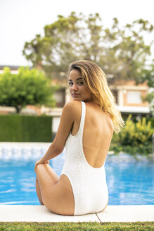 Young girl wearing swimsuit sitting on poolside - ACPF00270