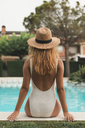 Young woman with straw hat sitting at poolside, rear view - ACPF00273