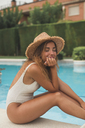 Smiling young woman with straw hat sitting at poolside - ACPF00279