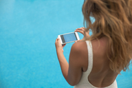 Young woman from behind doing a photo of the water in the swimming pool with a cell phone - ACPF00282