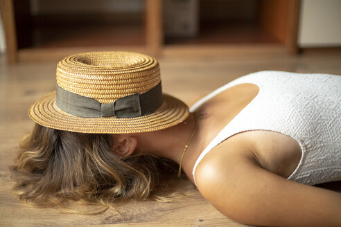 Unrecognisable young woman lying on the floor with a straw hat on her head - ACPF00288