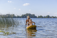 Father and daughter paddle boarding on lake - TCF05674