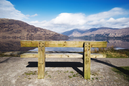United Kingdom, Scotland, view of a loch, empty wooden bench - RAEF02121