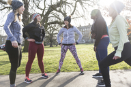 Female runners stretching and talking in sunny park - CAIF21592