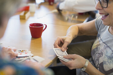 Senior woman playing cards with friend in community center - CAIF21673
