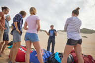 Male paragliding instructor talking to students on beach - CAIF21691