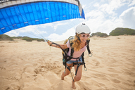 Smiling female paraglider running with parachute on beach - CAIF21694