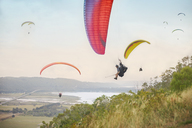 Paragliders in sky over landscape - CAIF21697
