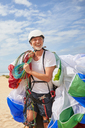 Smiling mature male paraglider carrying equipment and parachute - CAIF21700