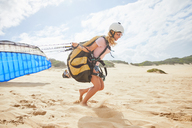 Female paraglider running with parachute on sunny beach - CAIF21703