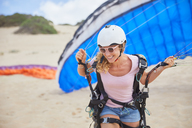 Smiling female paraglider with parachute on beach - CAIF21709