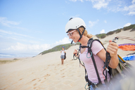 Smiling female paraglider with equipment on beach - CAIF21718